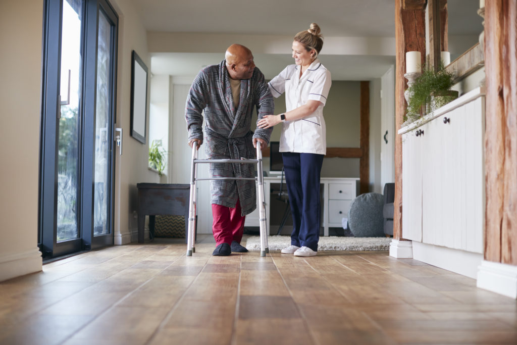 medical professional assisting man with walker